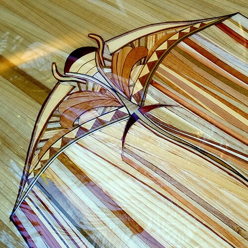 A wood surfboard with a Manta Ray inlay