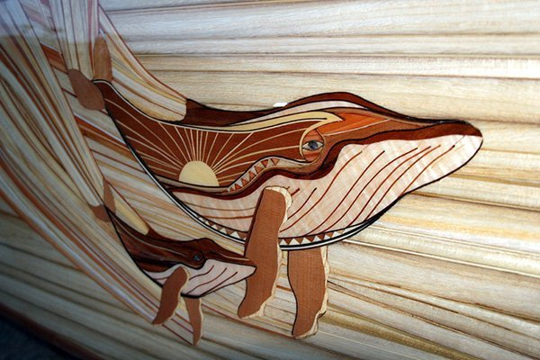 close up of wood design and mother of pearl detail on a michael rumsey decorative surfboard with whales titled ohana