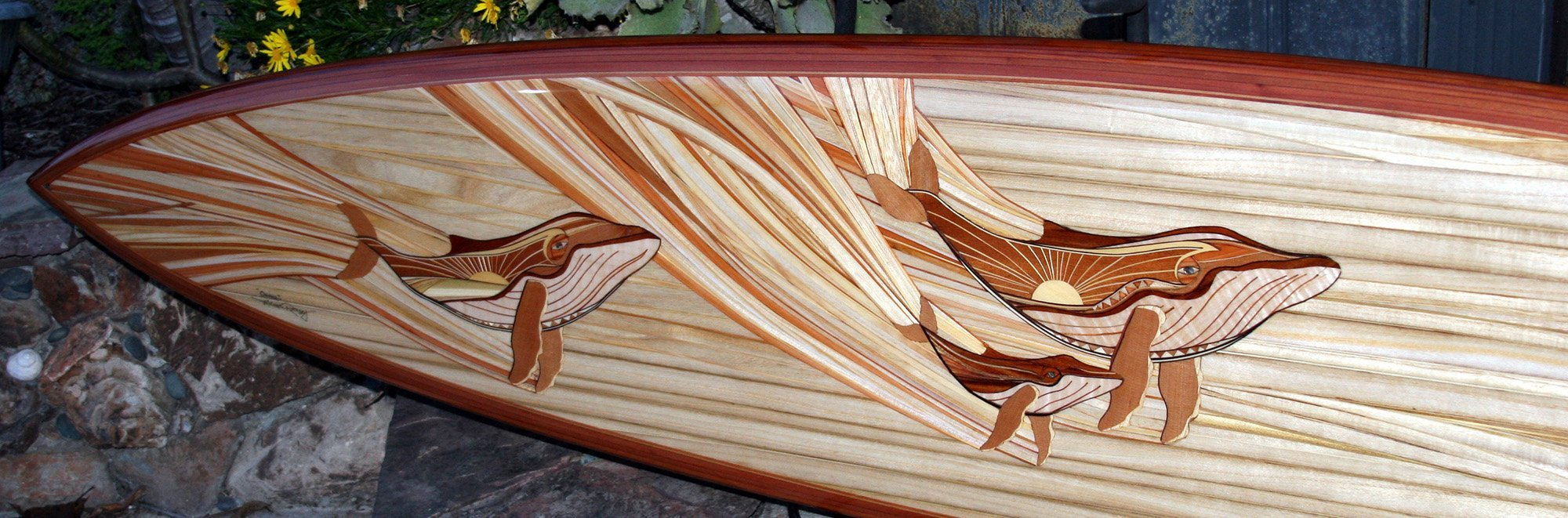 michael rumsey wood surfboard titled ohana with artwork depicting whales using only natural colors from reclaimed lumber