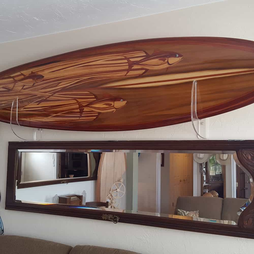 A beautiful wood inlay surfboard with three tunas in the design