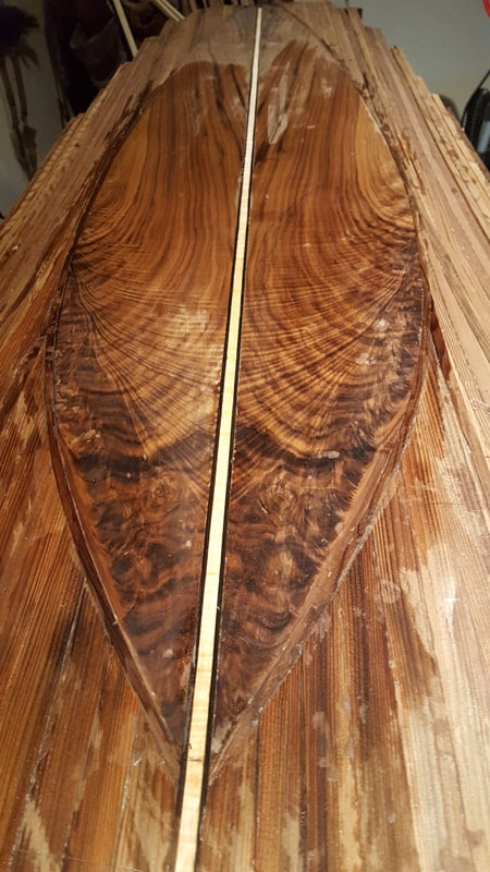 A surfboard in the process of being sanded and stained
