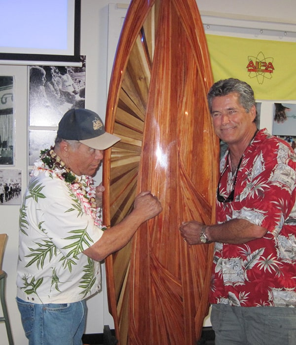 Michael Rumsey and Aipa knocking on a surfboard