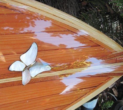 A beautiful wood inlay surfboard with abalone butterflies on it