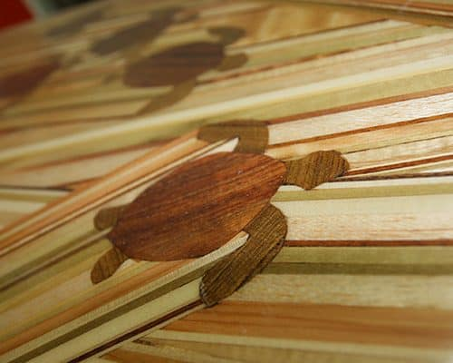 A close up of a beautiful wood inlay surfboard with the pattern being many turtles swimming