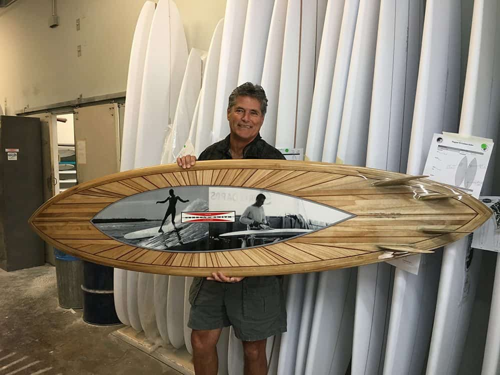 Michael Rumsey smiling and holding one of his surfboards