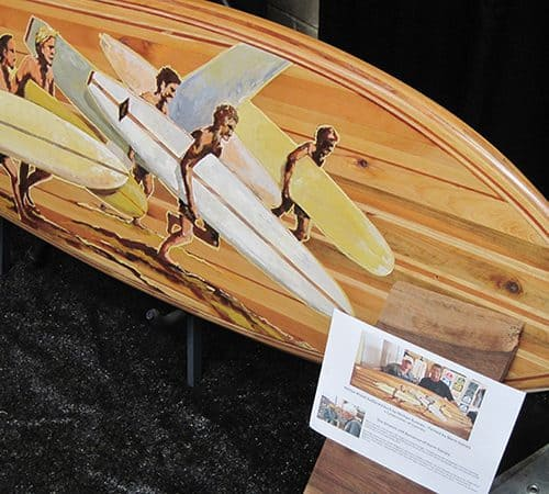A beautiful wood inlay surfboard with the pattern being five men with surfboards running towards the beach