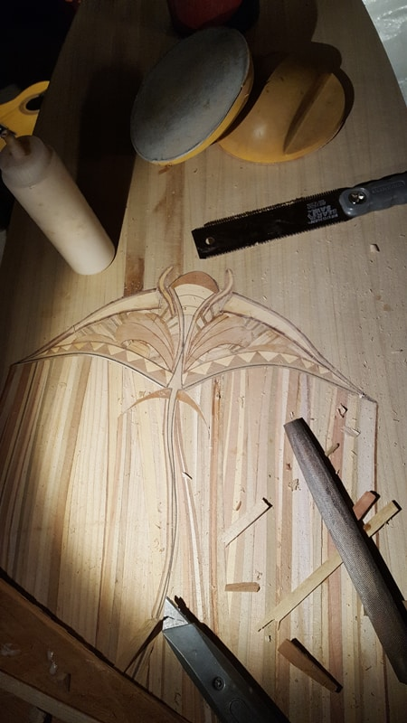 A surf board being worked on with a manta ray wood inlay
