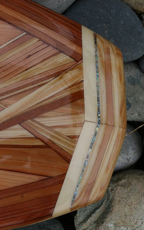 The tail of a wood surfboard with a abalone inlay