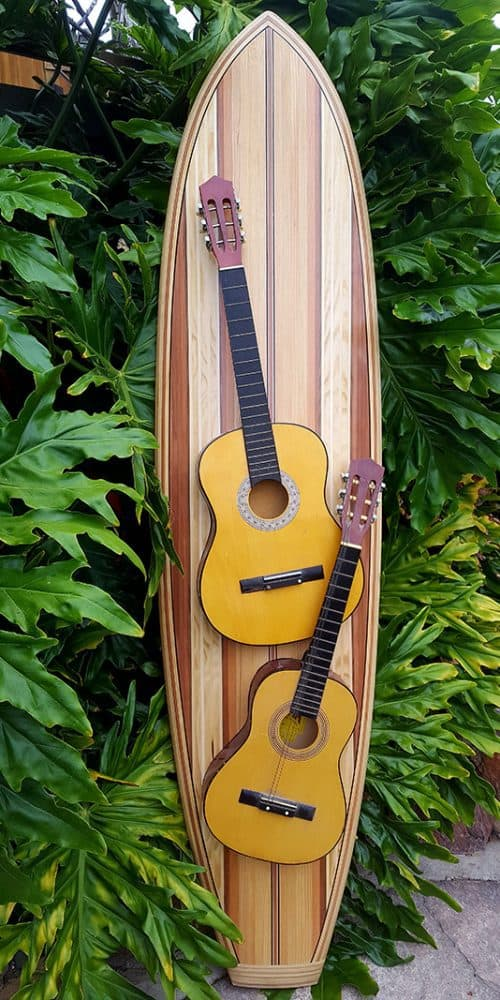 A wood inlay surfboard with two guitars hanging off it
