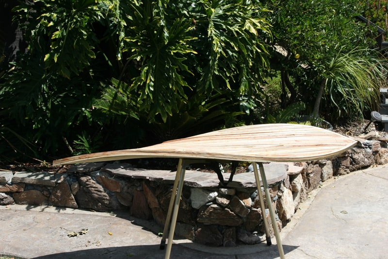 the process of shaping a board on a stand