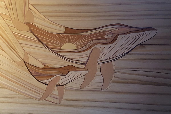 A beautiful wood inlay surfboard with the pattern of a family of whales