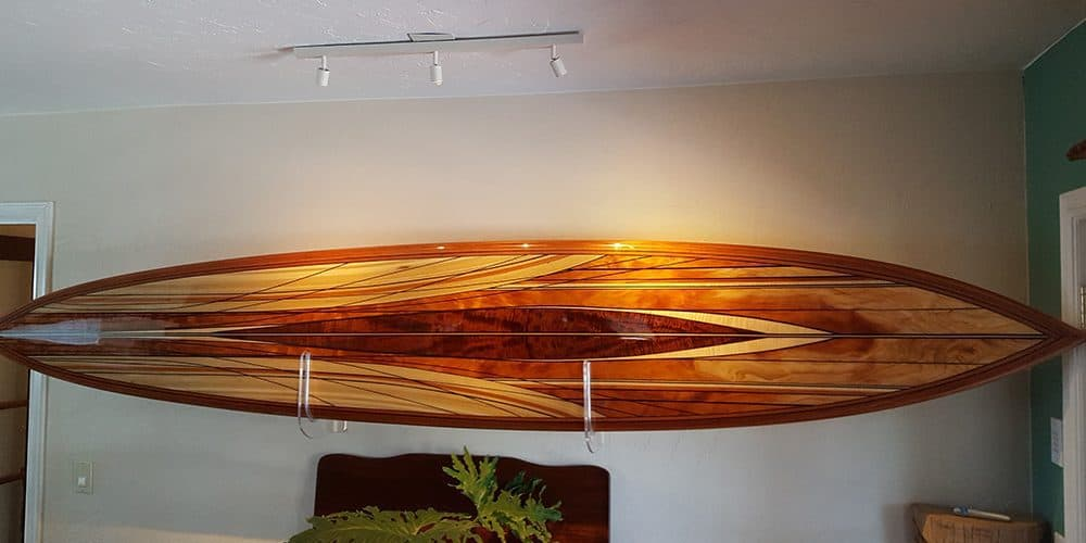 A beautiful wood inlay surfboard hanging on a wall