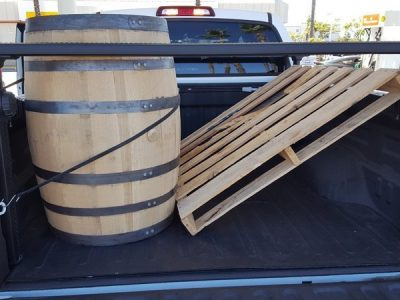 A wooden barrel and a pallet in the back of a truck