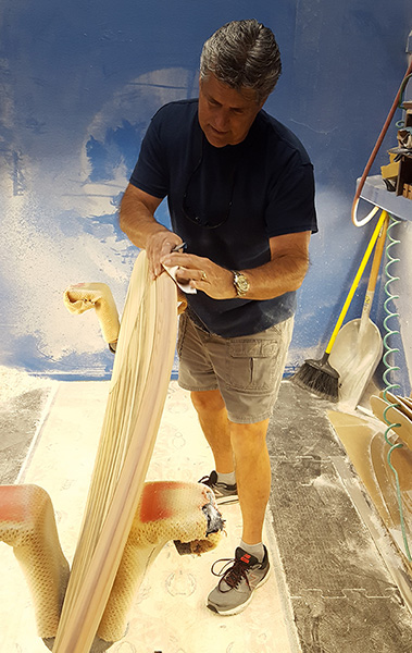 surfboard artist shaping decorative wood surfboards